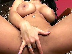 Long haired brunette Laura Lion with imposing boobs rubbing her trimmed pussy