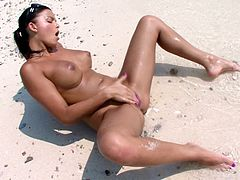 Lovely brunette with big boobs takes her bikini off and then lies down on the sand. After that she starts to finger her hot and wet pussy.