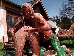 Clothed girls coated head to toe in chocolate sauce