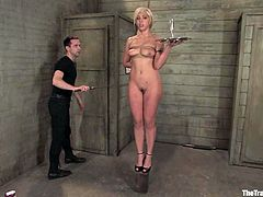 Hot babe gets tied up and put in the stocks. Later on the guy pinches her tits and fixes clothespins on them. Then he fucks this girl in her pussy.