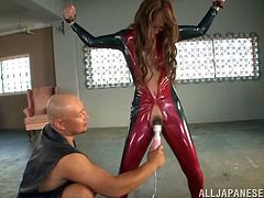 Stunning Japanese girl in red latex costume gets chained. So, she gets her hairy pussy toyed with a vibrator.