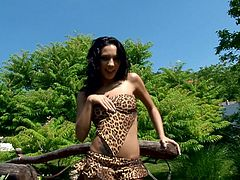 Sexy brunette Abelia wearing a leopard swimsuit is having some fun in the garden. She strokes her nice body and then sits down on the ground and pleases herself with ardent pussy fingering.