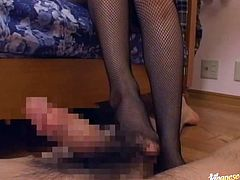 Sexy Japanese girl in sexy lingerie and fishnets sits on a bed giving a footjob to a guy. She also fondles her pussy.