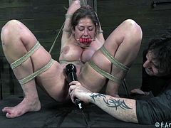 She's tied to a support beam in the basement and has a bit put in her mouth. She beaten and has pain inflicted on her. She's tied up in rope and can't escape as her master takes a vibrator to her pussy.