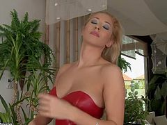 Tall blonde babe Karina Shay in black shoes and red pleather dress bares her juicy tits in front of black guy in the middle of the room. He cant keep his lips and hands off her titties.
