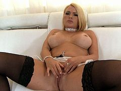 Filthy blond milf with voluptuous frame takes off her white lingerie remaining in black stockings before she sits on a couch with legs spread aside in order to pound her slit with fingers and later with dildo.