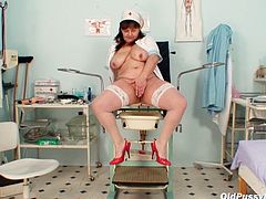 Nasty punani of rapacious fat granny in nurse lingerie and white stockings sits in the gynecological chair with her legs spread wide while drilling it with black dildo.