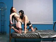 Arousing long haired Anastasia Pierce with natural boobs in lingerie gets tied up in uncomfortable position for bed by black haired bitch and just stays there while bitch is smoking
