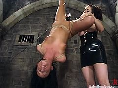 Adorable brunette girl gets tied up to a chair. After that another girl toys her pussy and hose her with cold water.