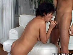 Short haired momma with big saggy boobs and white stockings enjoys in giving her young and lusty lover a hot blowjob on her knees in the living room on sofa