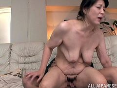 Japanese MILF lies on a sofa with her legs opened. She fingers and toys herself. After that she sucks a cock and gets fucked doggystyle at the same time.