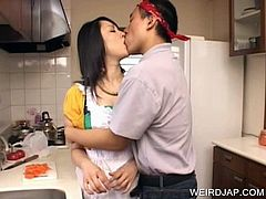 Brunette cute asian in apron gets boobs rubbed
