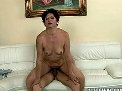 Naked cock hungry granny with short black hair and hanging tits gives head to yong turned on buck and rides on his cock to orgasm in living room on couch