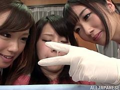 Asian girl comes to a hospital and sits down in a chair. She gets her hairy pussy licked and fingered by two sexy Japanese nurses.