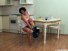 Frisky brunette chic masturbates on kitchen table