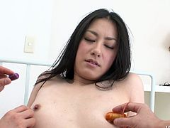Fuckable Japanese babe sits with her legs spread aside while two insatiable dudes stroke her hairy pussy and a pair of small perky tits with vibrators before they stick a dildo into her asshole for a hard bang.