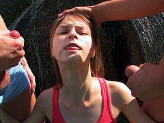 Sexy teen kneels and pleases two males in outdoor dirty threesome porn session