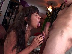 Mature long haired brunette whore with gigantic fake tits and good looking body seduces young stud with meaty sausage and gives him lusty blowjob in living room in close up