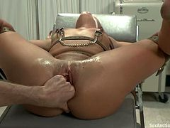 Brunette cutie lies on medical chair being tied up. The doctor fixes claws to her nipples and then toys her smooth pussy.