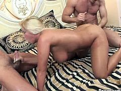 Lustful bitch is fucking hardcore in a threesome sex scene. She sucks the dick getting nailed hard from behind. Later she gets double penetrated and filled with double portion of jizz.