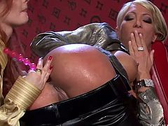 Alluring blond milf stands in doggy pose with her leather pants pulled down while a perverse red-haired slut pokes her asshole with anal beads in sizzling hot lesbian sex video by Tainster.