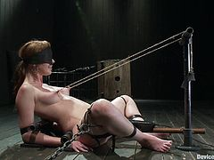 A cute redhead bitch gets pinned down by machines and then has her nipples yanked in this kinky bondage scene right here!