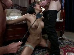 Stunning girl stands on her knees in a bedroom. She sucks a cock and gets whipped at the same time. After that she lies down on a sofa and gets fucked in both holes.