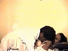 This couple is fornicating in a hotel room. They both are wearing white robes pleasing one another on a bed. The guy enjoys kneading big saggy boobs of his lover.
