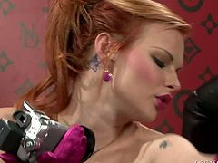 Mesmerizing red-haired babe holds a cam in her hands while another slut pets her aroused body through clothes in steamy lesbian sex video by Tainster.