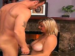 Slutty cock loving skilful blonde Kala with big natural knockers and curvy body gets naked while teasing handsome Bob and gives memorable titjob session in close up by fireplace.