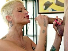 She is on her knees and rubbing her guy's penis & deepthroating like a real pro. This tattooed whore is putting all her dedication to satisfy this guy who is filming her. Her lustful eyes says that she just wants a load of hot jizz on her face & when he does that, she enjoys it with her eyes closed.