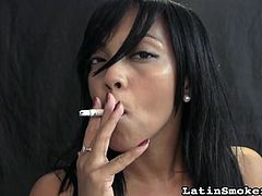 Horny brunette smokes a cigarette while teasing and posing like a naughty slut