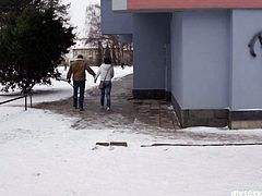 Darkhead chick plays with snow outdoor so her hands are freezed. The guy invites her indoor where they have a cup of tea. They start kissing sensually.