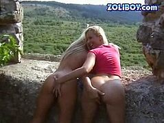 Two young perv lesbian cuties flaunt their delicious round butts outdoors