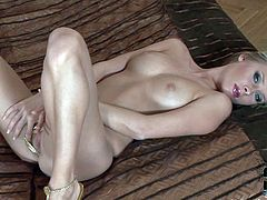 Deni M is an eye-popping adult model with beautiful blue eyes and blond hair. She poses topless in her string thong and shoes on the bed. She displays her firm perfect tits and flashes her pussy.