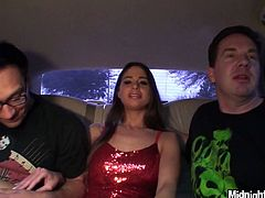 Spoiled brunette babe sits between two horny men on car seat with legs wide open while they rub her tights and big firm tits with their spoiled hands in peppering MMF sex clip by Pornstar.