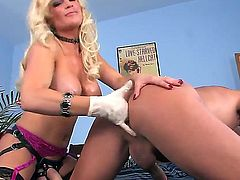 Freaky dude Vin Deacon is standing doggy at front of blonde chick Diamond Foxxx and getting his asshole fisted with her gloved hand.