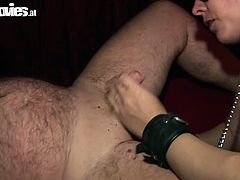 Blond slut wearing leather BDSM attributes dominates on her sub. She chains him to the couch so he can't make a move. The she puts drops of hot red wax on the tip of his dick.