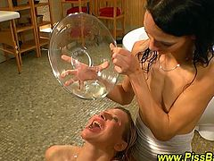See a hot and busty German blonde and her slender brunette friend making out while some dudes cover them in warm fresh piss.