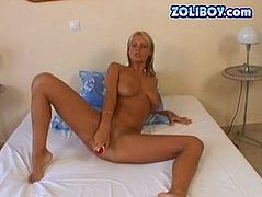 Busty tanned blond hottie stretches vulvar lips and masturbates with a dildo