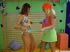 Nasty brunette girl and blond skank with big boobs are playing with hula hoop in a gym wearing sporty outfits. The blond one gets her big tits rubbed and suckled later. Then she enjoys pussy licking action.