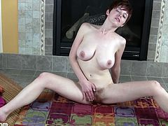 Get a load of this brunette's huge natural tits in this hot solo video where she takes off her panties to play with her bush in front of the fire place.