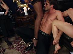 Maitresse Madeline sticks her feet in Lance Heart's face. He takes off her nylons and he licks her toes. After a while, the mistress called Daisy to join the party. Daisy makes him suck on the heel of her boot and steps on his cock.