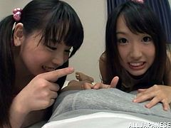 Two adorable Japanese teens are having fun with some guy indoors. The man shows his prick to the hotties and lets him lick and rub it.