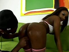 Ample black babe in white sporty lingerie and fishnet stockings bends over a couch to welcome a finger fuck from rapacious black dude before she squats down in front of him to give him a thorough blowjob.