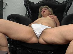This horny mature is lost in her masturbation. Look how this naked slut who is only in her panties moans while she is crushing her nice pair of boobs. Then she starts rubbing her pussy beneath her panties. Finally it comes out and she shows us her hairy fussy which she is fingering hard. Watch!