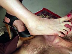 blonde dominatrix sticks her feet in slave's face
