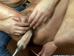 Fuckable curvy brunette grandma hooks up with perverse tattooed daddy. He pokes her bushy soaking cunt with dildo machine as she lies on her back with legs wide open.