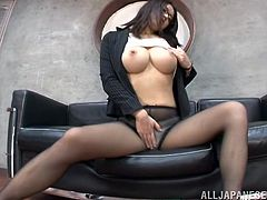 This elegant Japanese babe in glasses and pantyhose with big tits and office uniform is having fun giving a footjob to a dude.