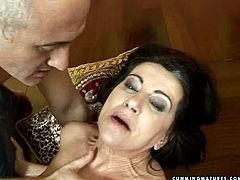 Ample brunette mom lies on the floor with legs spread wide while a horny grey-haired man strokes her hairy punani with vibrator and later rubs it with his hand.